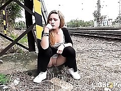 Girl takes a piss by the train tracks