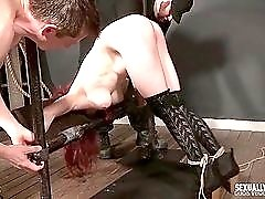 Slave in a wooden stockade gets mouth fucked