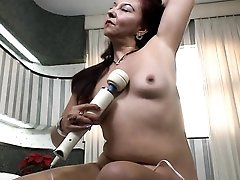 Latina mommy with a vibrator gets hot and bothered in bed